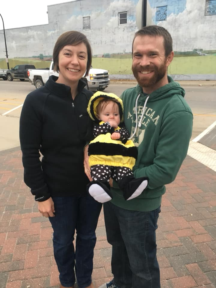 Bill and Melissa Frederick holding their daughter dressed in a bee costume.